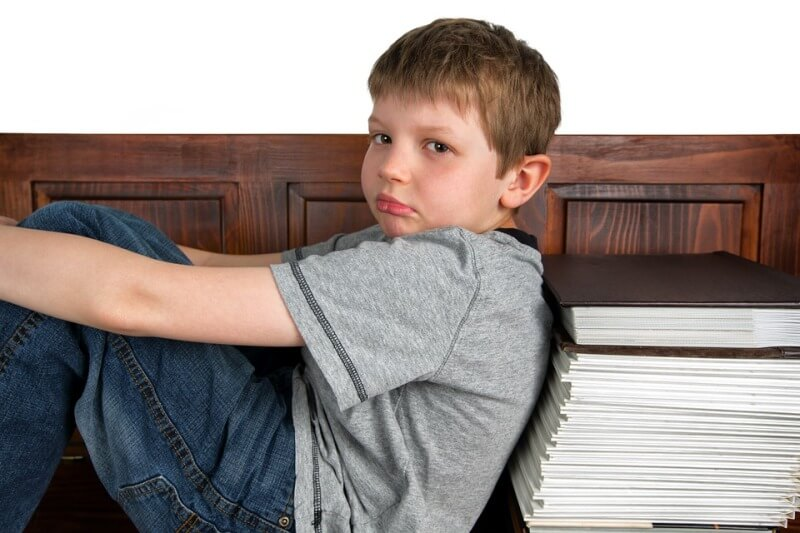 Child sitting his back on a pile of books